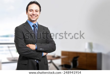 Confident young manager standing with crossed arms - stock photo