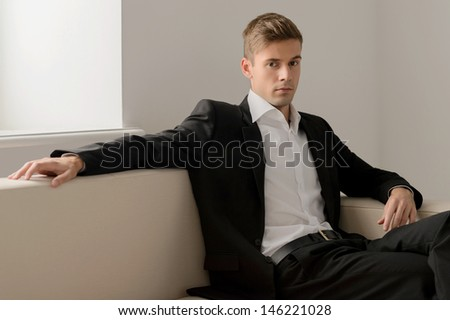 Confident young men. Handsome young men in formalwear sitting on the couch and looking at camera - stock photo