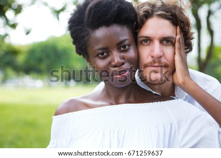 Confident young mix-raced couple posing at camera