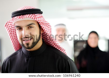 Confident young Saudi business executive with his team in the background - stock photo