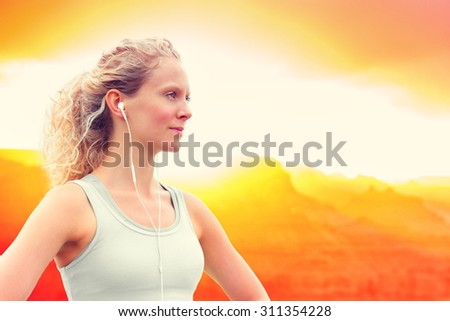 Confident young sporty woman listening to music. Caucasian female is in sportswear. She is using earphones during sunset. - stock photo