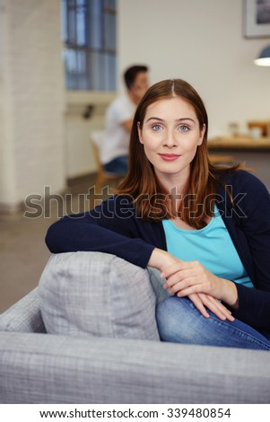 confident young woman at home on her sofa with a man sitting in the background of the living room