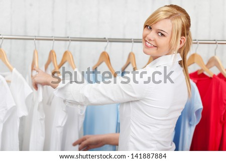 confident young woman choosing shirt in a shop - stock photo
