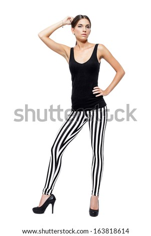Confident young woman dressed in a leggings and shirt, isolated on white background