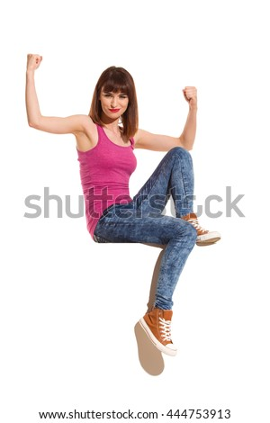 Confident young woman in pink shirt, jeans and brown sneakers sitting on a top and flexing muscles. Full length studio shot isolated on white.