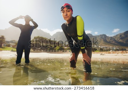 Confident young woman in wet suit standing in water looking at camera. Young triathletes preparing for competition. Triathlon training at the lake. - stock photo