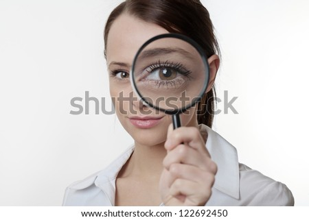 Confident young woman looking through a magnifying glass