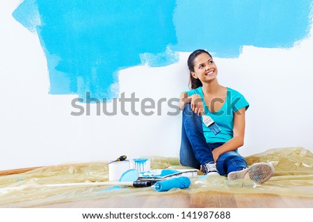 confident young woman portrait while painting new apartment renovating with blue color paint - stock photo