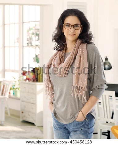 Confident young woman smiling at home with hands in pockets.