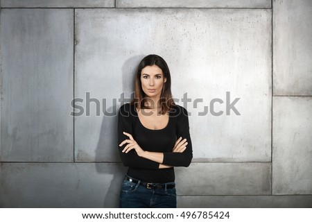 Confident young woman standing arms crossed by wall, looking at camera.
