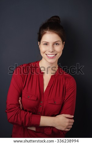 Confident young woman with a beaming smile standing against a dark background with folded arms looking at the camera - stock photo
