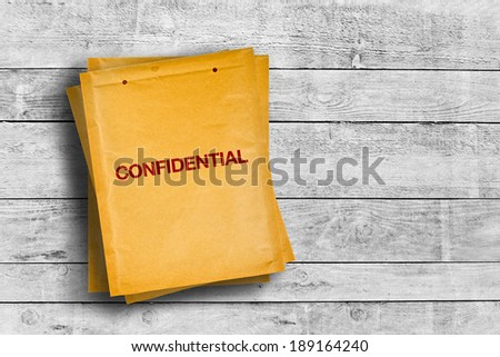 Confidential stamp on yellow envelope placed on wooden table - stock photo
