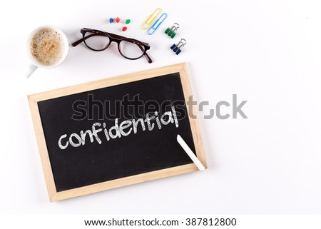 Confidential word on chalkboard with coffee cup and eyeglasses, view from above - stock photo