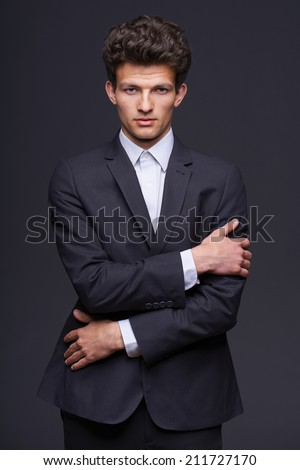 Confindent serious business man, fashion model with modern hairstyle, over gray background