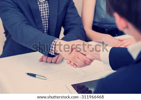 Confirmation of the transaction. Business shaking hands in the office - stock photo