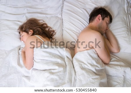 Conflict and relation difficulties concept. Couple is sleeping back to each other in bed.