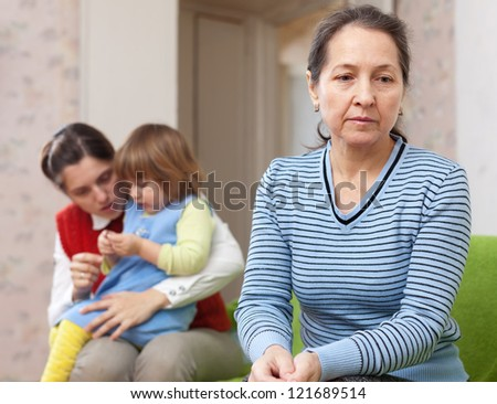 Conflict between generations. Sad mature grandmother against daughter with baby - stock photo