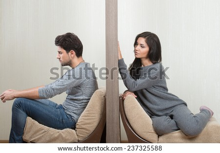 Conflict between man and woman sitting on either side of a wall - stock photo