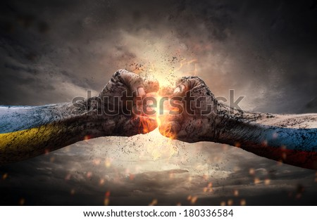 Conflict, close up of two fists hitting each other over dramatic sky - stock photo