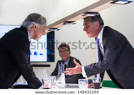 Conflict in office : Business executive arguing with his boss at meeting over latest sales figures with others watching - stock photo