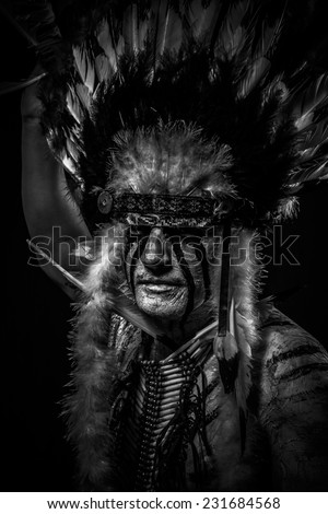 Conflict Native, American Indian chief with big feather headdress - stock photo