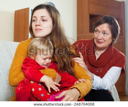 Conflict of intergenerational. Mature woman and young mother with crying  baby after quarrel at home - stock photo