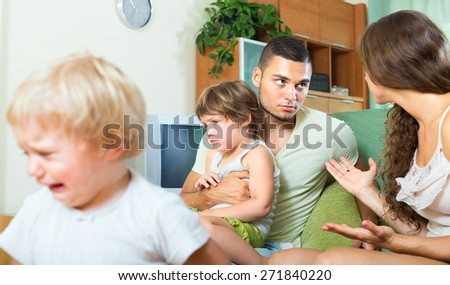 Conflict of young parents in the presence of daughters at home - stock photo