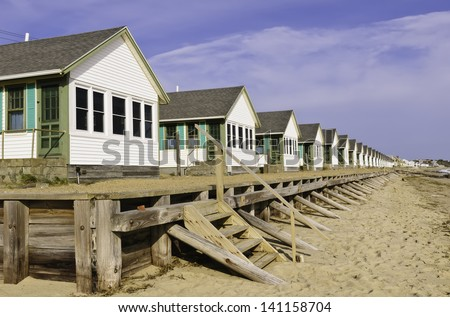 Conformity at the beach: Long row of identical white beach cottages in Cape Cod, Massachusetts - stock photo