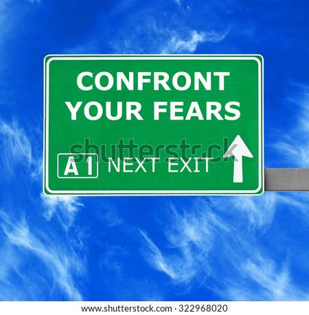 CONFRONT YOUR FEARS road sign against clear blue sky - stock photo