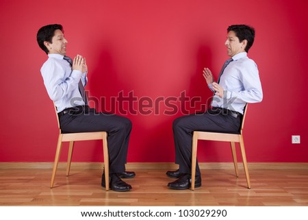 Confrontation between two twin businessman sited next to a red wall - stock photo