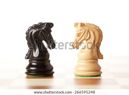 Confrontation - white and black chess knights - stock photo