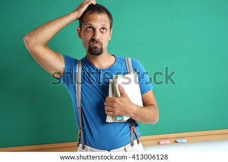 Confused adult student remember something. Photo adult man near blackboard, education concept - stock photo
