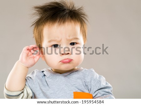 Confused baby boy hand touch ear - stock photo