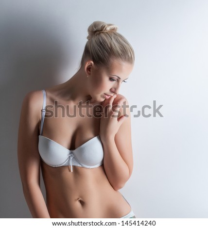 Confused beautiful blonde posing in white lingerie - stock photo