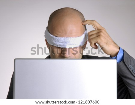 Confused blindfolded bald head man using a computer. - stock photo
