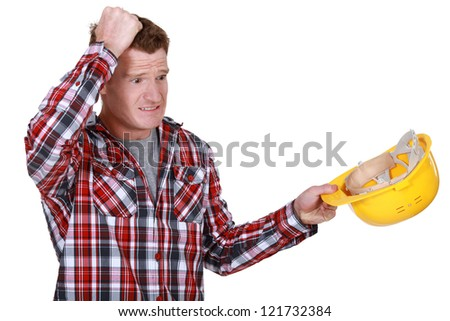 Confused builder removing hard hat - stock photo