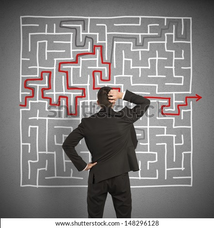 Confused business man seeks a solution to the big labyrinth - stock photo