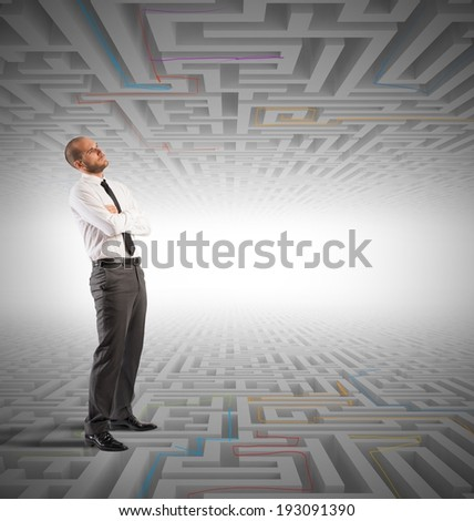 Confused business man seeks a solution to the labyrinth - stock photo