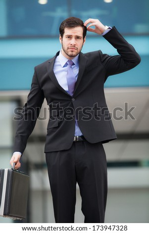 confused businessman in front of an office building with a briefcase