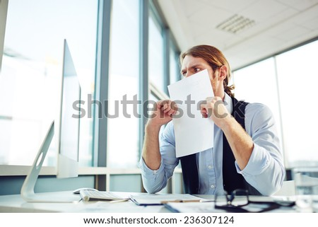 Confused businessman looking at computer monitor with paper by his face - stock photo