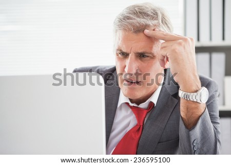 Confused businessman looking at his laptop in his office - stock photo