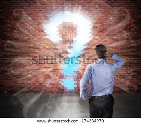 Confused businessman standing in front of a brick wall with question mark hole and question marks flying into the room - stock photo