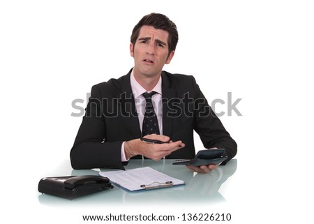 Confused businessman with a calculator