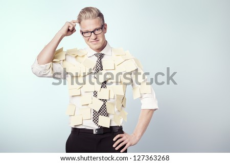 Confused businessman wondering while being covered by many empty yellow post-it notes with space for text, isolated. - stock photo