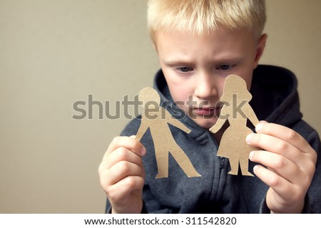 Confused child with cutting paper parents, family problems, divorce, custody battle, suffer concept  - stock photo