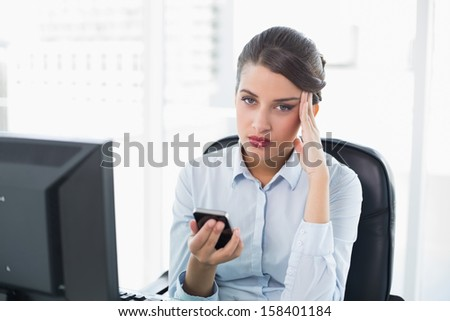 Confused classy brown haired businesswoman holding a mobile phone in bright office - stock photo