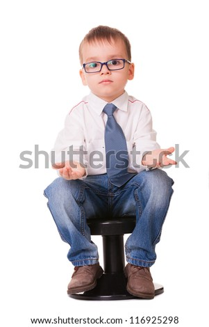 Confused clever kid in jeans and shirt sitting on small chair isolated on white background - stock photo