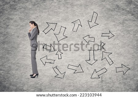 Confused concept with Asian business woman thinking with hand drawing graphic behind her. - stock photo