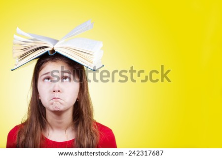 Confused cute little schoolgirl  with a open book on her head, isolated over yellow background.