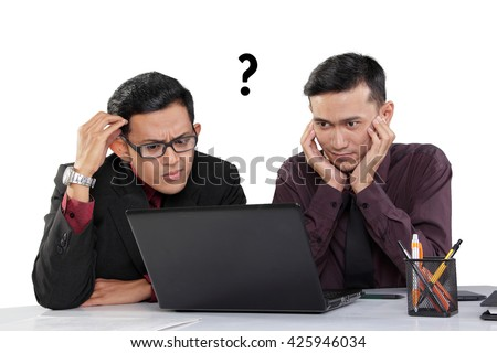 Confused face expressions of two Asian businessmen looking at a laptop on the desk, isolated over white background